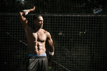 Bare-chested muscular young man posing by wire fence