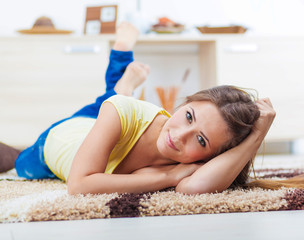 Portrait of attractive young woman lying down on carpet in the living room.