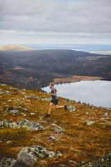 Man running on rocky cliff top, Keimiotunturi, Lapland, Finland