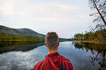 Man looking out to lake, Kesankijarvi, Lapland, Finland