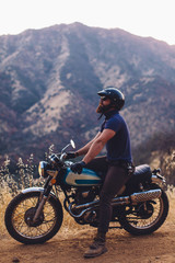 Man sitting on motorcycle in mountains