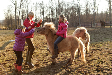 Young girl riding pony, mother and sister standing beside them