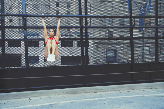 Portrait of young woman swinging on metal bar outdoors