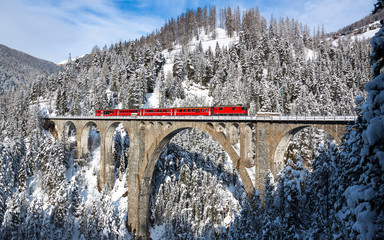 Train ride over bridge of snow covered mountains and trees