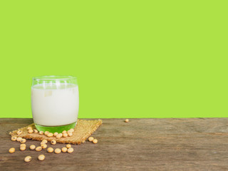Milk  and soy bean on wooden table of green color background