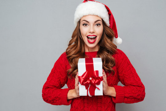 Happy excited woman in santa claus hat with gift box