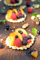 Fresh red, black raspberry and currant, peach, honey on waffle on wooden texture close up