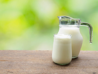 Milk jug and yogurt in glass on wooden table of natural