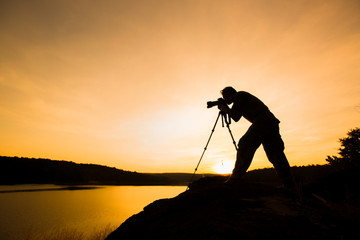 photographer silhouette with sunset or sunrise