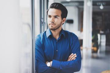 Portrait of successful confident hispanic businessman standing close from the window in modern office.Horizontal,blurred background.