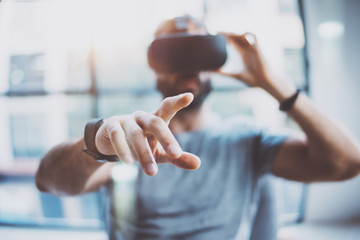 Closeup of male hand.Bearded young man wearing virtual reality goggles in modern coworking studio. Smartphone using with VR headset in office. Horizontal, blurred.