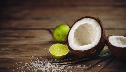 Close-up of fresh coconut and sliced lime on wooden table.