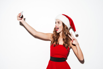 Woman in red santa claus costume making selfie with cellphone