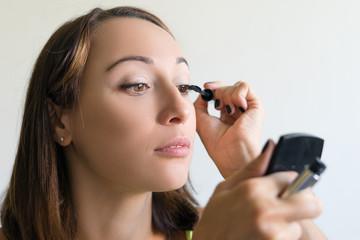 Girl paints eyelashes brush