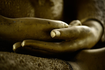 gold hands of buddha statue in post meditation. Buddha sits with hands in meditation position