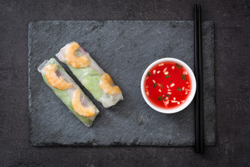 Vietnamese rolls with vegetables, rice noodles and prawns on black slate