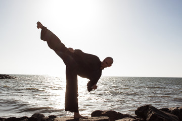 practicing karate on the beach on a sunny day
