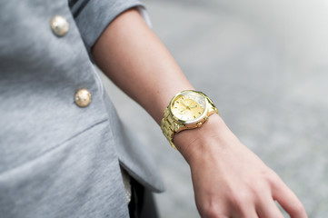 Fashion woman with golden watch on hand