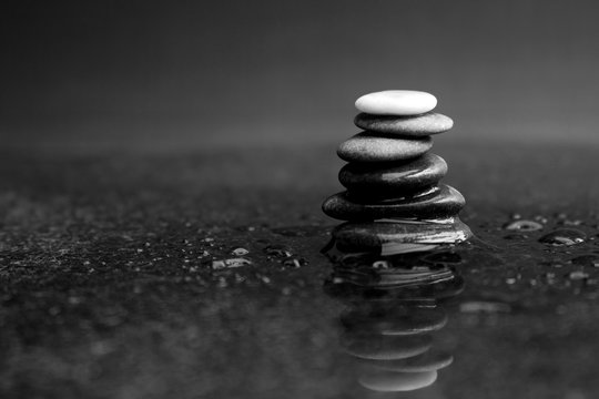 Pebble stack in black and white with black pebbles and one white on the top lying on wet marble