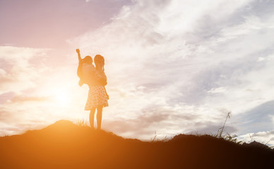 Silhouettes of mother and little daughter walking at sunset