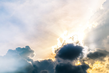 Beautiful evening skyscape. Sun's rays shine through hole in black clouds after rain. Sky, Golden sky. Natural background. Inspirational concept.