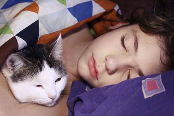 preteen handsome boy with cat sleeping