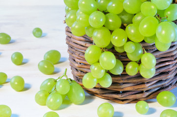 Green grape in basket on wooden table