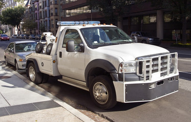 Tow truck and vehicle violation. in urban setting. Horizontal.