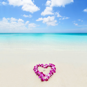 Two wedding rings in a heart lei on beach vacation. Hawaiian flower necklace lying on the sand in the shape of a heart with rings for marriage proposal in tropical vacation destination honeymoon.