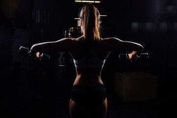 Beautiful fitness woman with lifting dumbbells .