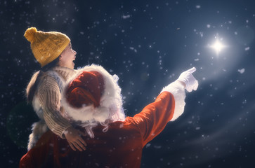 girl and Santa Claus looking at Christmas star