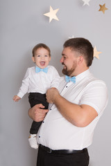 Portrait of a father with his baby boy in elegant clothes during the holiday