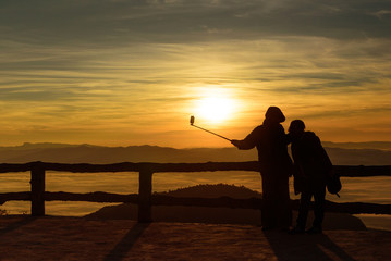 silhouette style of couple on the top of view point in the mountain while selfie during sunrise and sea of fog or mist