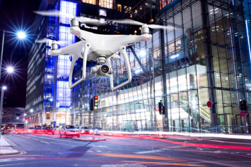 Hovering drone taking pictures of city of London at night