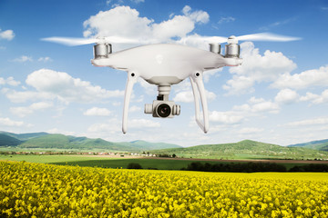 Hovering drone taking pictures of canola field and green hills