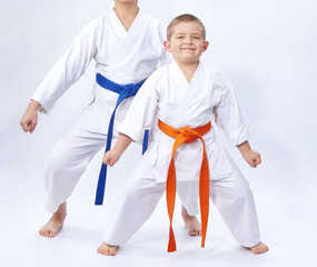Boys in karategi are standing in the rack karate