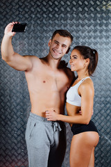Attractive fitness couple in sports clothes is making selfie indoor.