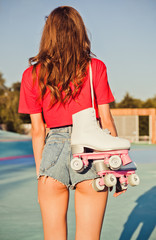 Girl with long dark hair is back with roller skates on her shoulder. Warm summer evening in the skate park.