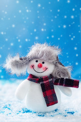 Christmas snowman doll on a winter background. Christmas card.