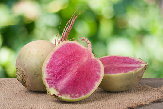 One whole and sliced watermelon radish on a wooden table with blurred garden background