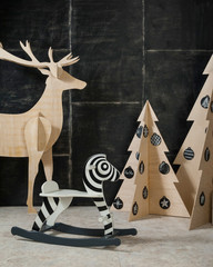 New Year's and Christmas decoration deer and fir plywood and wood on a dark background