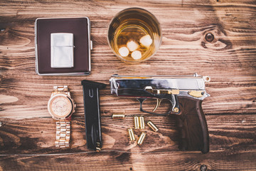 whiskey, watches, silver pistol on the table
