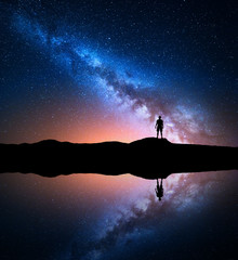 Milky Way. Night sky with stars and silhouette of a standing alone man on the mountain near the lake with reflection in water. Milky way and man on the hill. Galaxy and silhouette of a man. Universe
