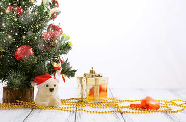 Christmas tree, gold gift box, balls, toy bear, candies and decorations on retro vintage white table isolated on white background with shiny snowfall