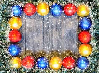 New year theme: christmas decoration and balls on grey retro stylized wood background with shiny snowfall