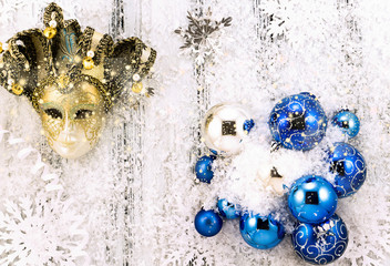 New year theme: Christmas tree white and silver decorations, blue balls, snow, snowflakes, serpentine and golden mask on white retro stylized wood background with shiny snowfall