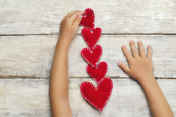 Kid's hands put toy hearts