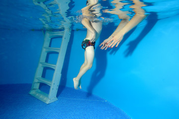 A little boy POPs up from the bottom of the pool to the surface, and the coach catches him. The view from under the water. Landscape orientation