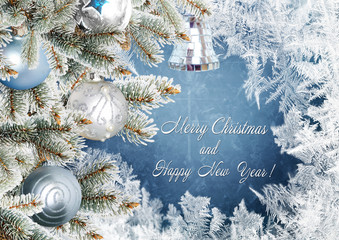 Christmas greeting card with pine branches and balls on the frosty background