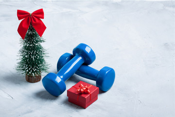 Christmas sport composition with dumbbells, red gift box, christ